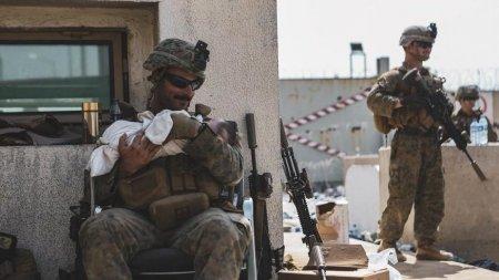 Imagini emotionante cu soldatii americani leganand bebelusii aban<span style='background:#EDF514'>DONATI</span> pe aeroportul din Kabul