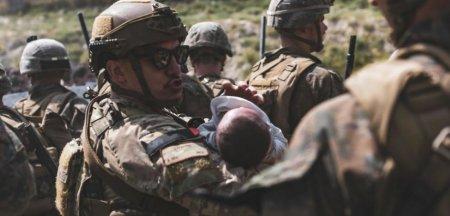 Scene emotionante pe aeroportul din Kabul. Soldatii americani, nevoiti sa aiba grija de bebelusii aruncati peste gard de parinti disperati FOTO