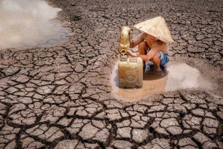 Seceta in Vietnam: Imagini <span style='background:#EDF514'>CUTRE</span>muratoare cu un copil care strange ultimele picaturi de apa de pe un camp ars de soare