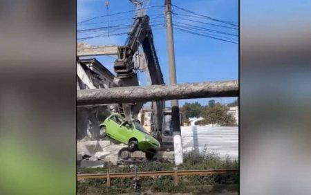 Masina ridicata de un excavator si mutata peste gard, pe un santier din Chisinau VIDEO