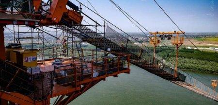 Cablul principal al <span style='background:#EDF514'>PODU</span>lui peste Dunare de la Braila, in curs de montare. Imagini spectaculoase din timpul operatiunii VIDEO