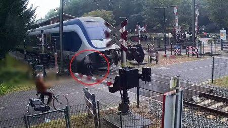 VIDEO O femeie a riscat sa-si piarda viata, trecand la cativa centimetri de un tren