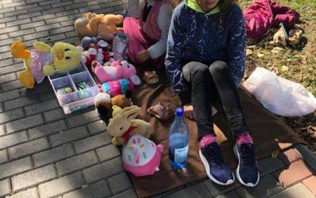 Doua fetite din Roman isi vand plangand jucariile pe strada pentru ca parintii sa aiba bani de facturi